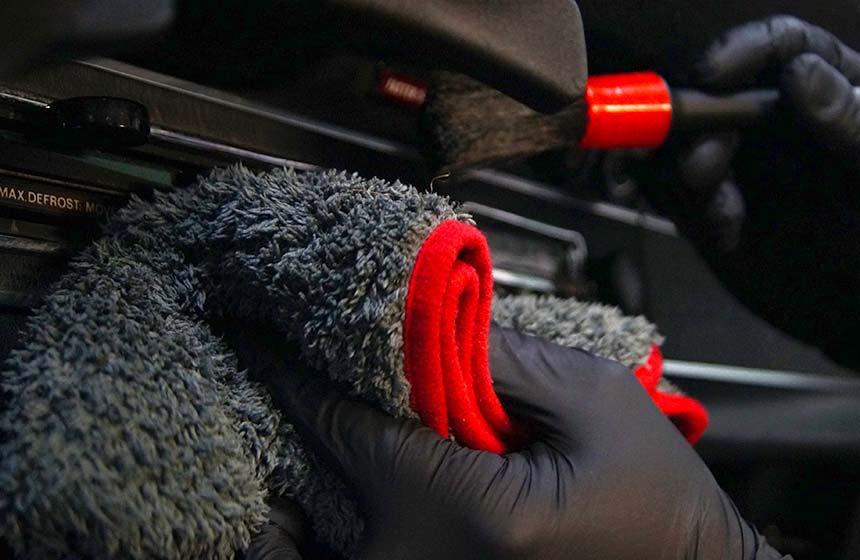 Innenraumpflege und Veredelung mit Pinsel eines Amaturenbretes im Auto